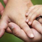 Kahden aikuisen ja pienen lapsen kädet päällekkäin.