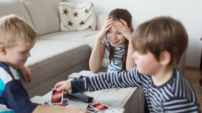 Kaksi poikaa ja tyttö pelaavat Uno-peliä pöydän ääressä.