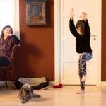 Tyttö voimistelee kotona äidin katsellessa.