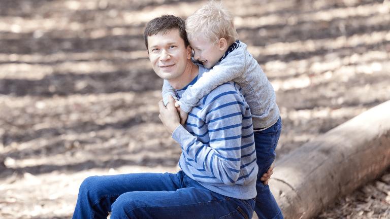 Poika kiipeämässä isän harteille.