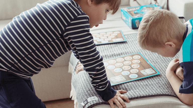 Kaksi poikaa pelaa lautapeliä sohvalla.