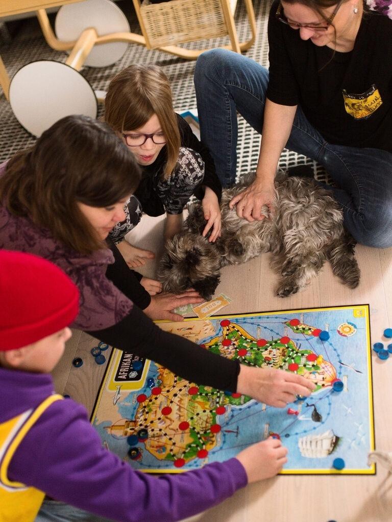 Perhe pelaa yhdessä Afrikan tähteä ja koira makaa lattialla.