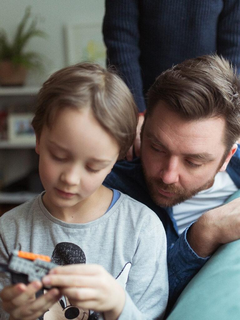 Isä katsoo kun lapsi tarkastelee legoista tehtyä lelua.
