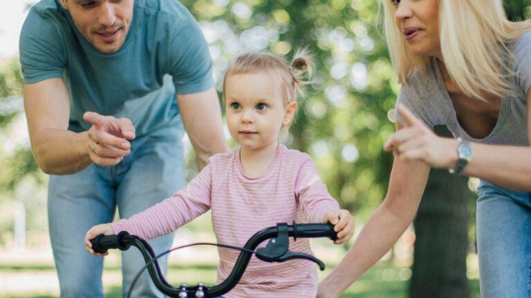 Äiti ja isä opettavat tyttöä ajamaan polkupyörällä